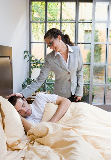 Stock Photo: 1589R-69948 Businesswoman saying goodbye to man in bed