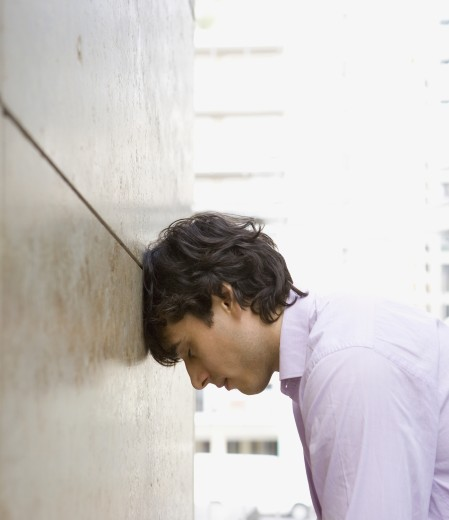 Stock Photo: 1589R-69968 Businessman leaning head against wall