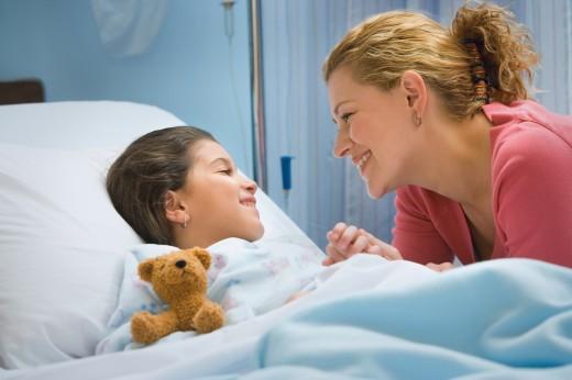 Mother smiling at daughter in hospital bed : Stock Photo