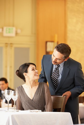Hispanic man pushing in wife's chair at restaurant : Stock Photo