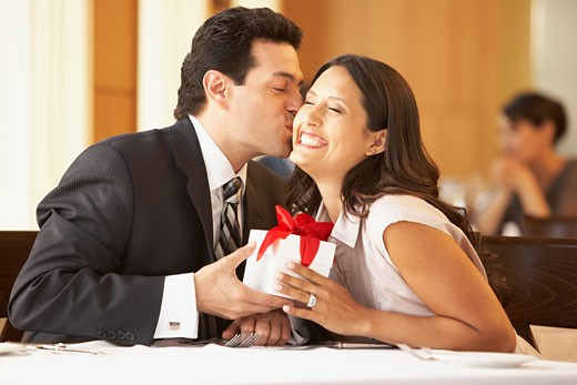 Stock Photo: 1589R-70153 Hispanic man giving gift to wife at restaurant