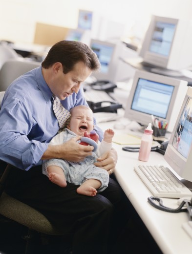 Stock Photo: 1589R-70286 Businessman holding crying baby at desk