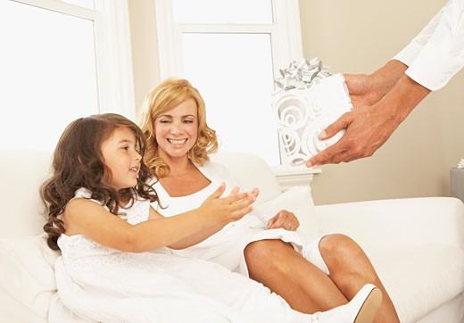 Hispanic girl receiving gift from father : Stock Photo