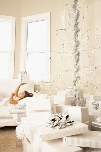 Hispanic girl with gift next to artificial Christmas tree : Stock Photo