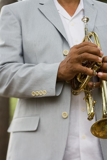 Stock Photo: 1589R-70464 Senior African man holding trumpet