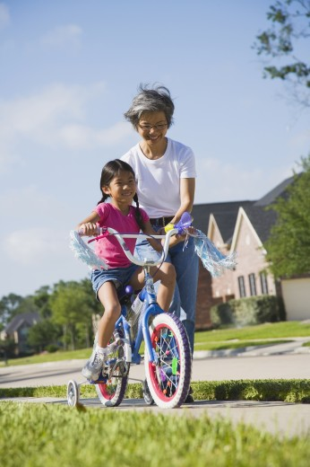 Asian mother helping daughter ride bicycle : Stock Photo