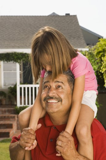 Stock Photo: 1589R-70599 Hispanic grandfather carrying granddaughter on shoulders