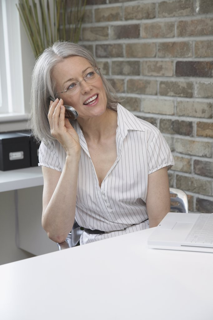 Middle-aged woman talking on cell phone : Stock Photo