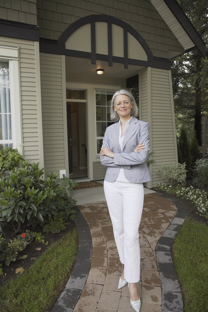 Portrait of middle-aged woman in front of house : Stock Photo