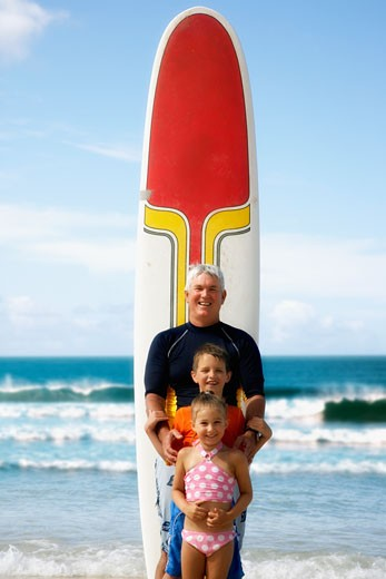 Grandfather and grandchildren in front of surfboard at beach : Stock Photo