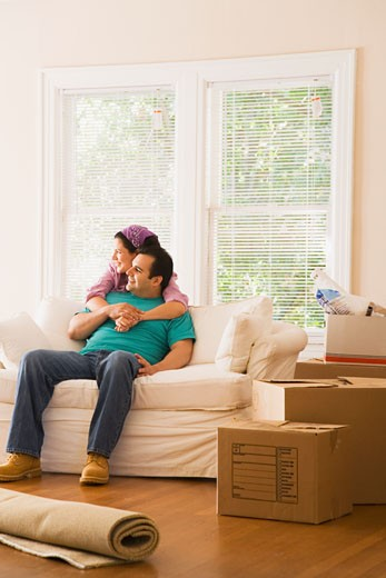 Hispanic couple on sofa in new home : Stock Photo