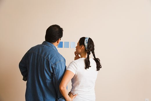 Hispanic couple looking at paint swatches : Stock Photo
