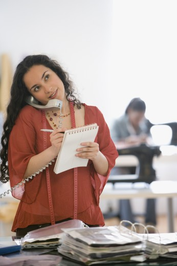Stock Photo: 1589R-71016 Hispanic seamstress using telephone in design workshop