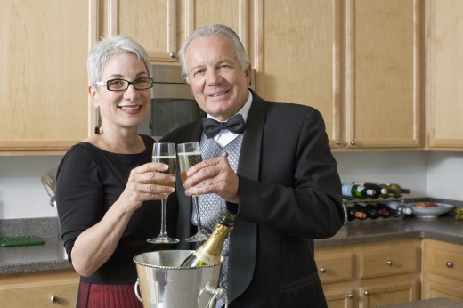Stock Photo: 1589R-71083 Well dressed senior couple toasting with champagne in kitchen