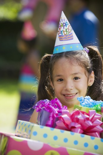 Hispanic girl carrying gifts at outdoor birthday party  : Stock Photo
