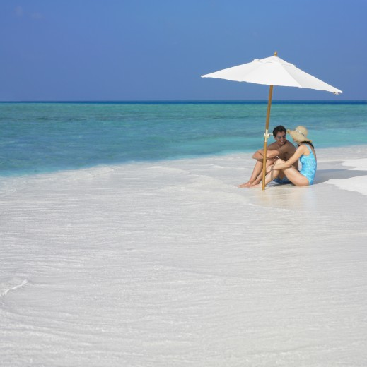 Stock Photo: 1589R-71421 Couple sitting under umbrella at beach