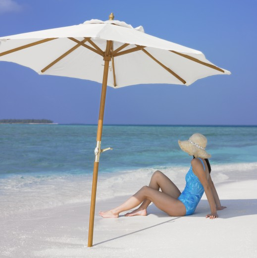 Stock Photo: 1589R-71422 Woman sitting under umbrella at beach