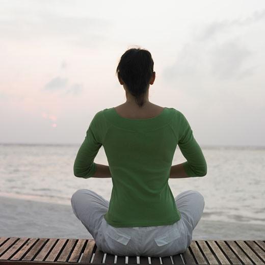 Woman meditating at beach : Stock Photo