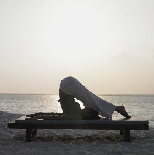 Woman practicing yoga at beach : Stock Photo