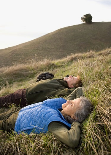 Stock Photo: 1589R-71602 Couple laying in grass on hillside