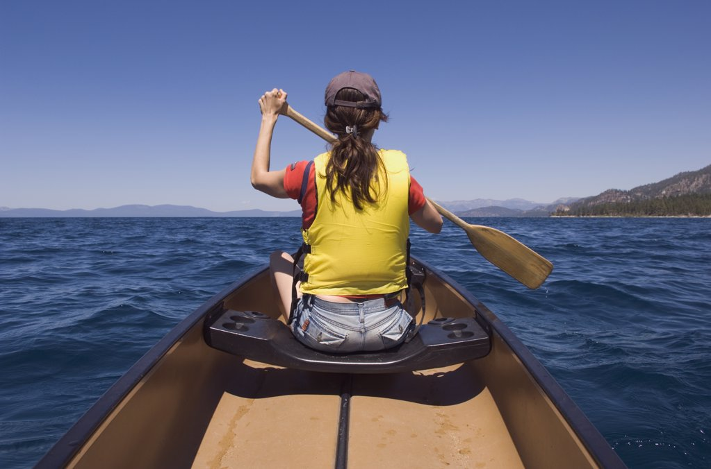 Rear view of woman paddling canoe : Stock Photo