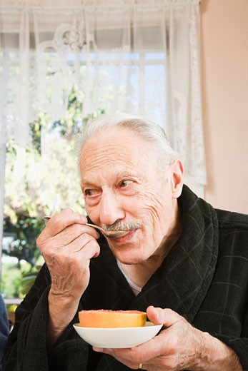 Senior man eating grapefruit : Stock Photo