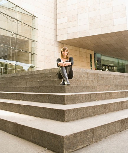 Stock Photo: 1589R-71883 Woman sitting on corner of urban stairs