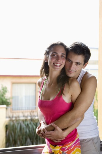 Couple hugging next to open window : Stock Photo