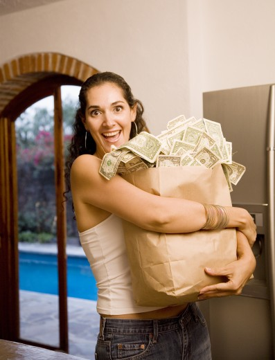 Stock Photo: 1589R-72056 Hispanic woman holding bag of money