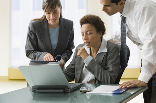 Multi-ethnic businesspeople looking at laptop : Stock Photo