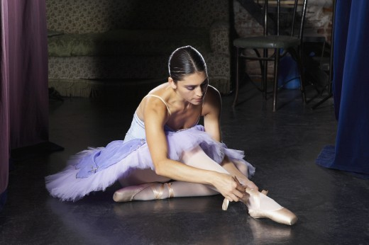Stock Photo: 1589R-72391 Hispanic female ballet dancer tying shoe