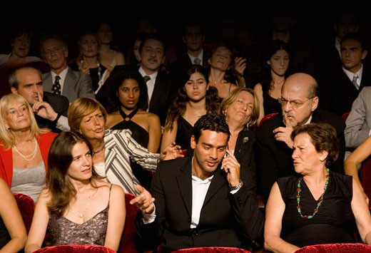 Stock Photo: 1589R-72457 Hispanic man talking on cell phone in theatre