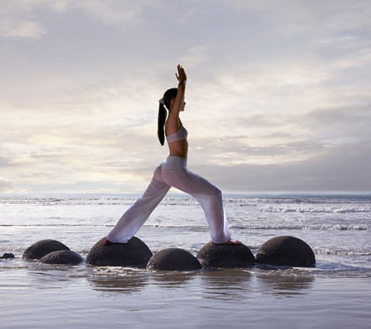 Stock Photo: 1589R-72484 Pacific Islander woman practicing yoga at beach