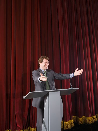 Businessman behind podium on stage : Stock Photo
