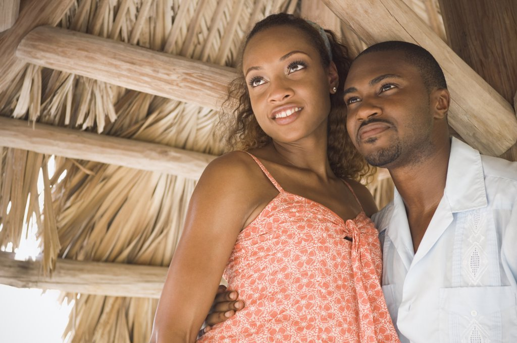 Stock Photo: 1589R-72668 African American couple hugging in grass hut