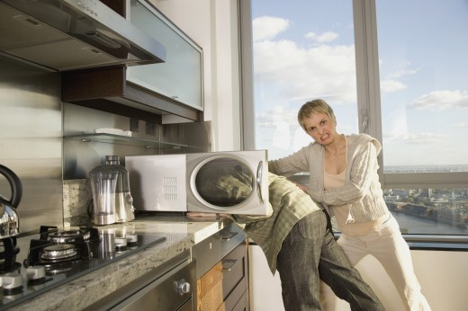 Stock Photo: 1589R-72685 Hispanic woman pushing husband's head in microwave