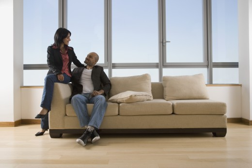 Multi-ethnic couple sitting on sofa : Stock Photo