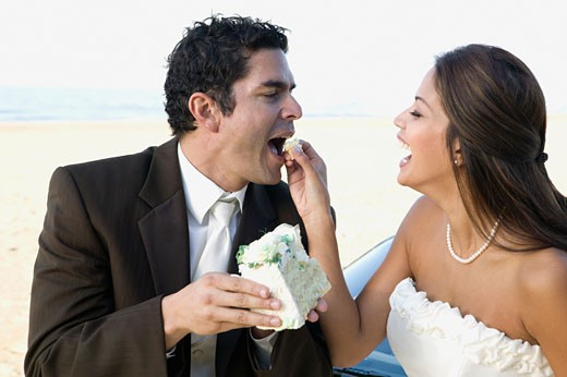 Hispanic newlyweds eating cake : Stock Photo