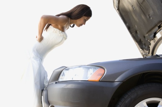 Stock Photo: 1589R-72928 Hispanic bride looking under hood of car