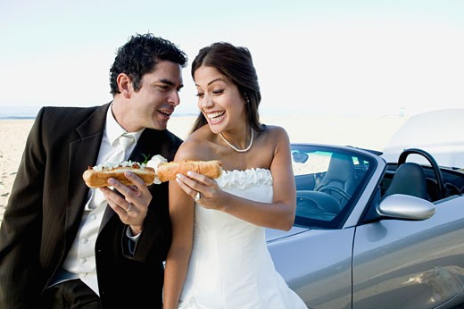 Hispanic newlyweds eating hot dogs : Stock Photo