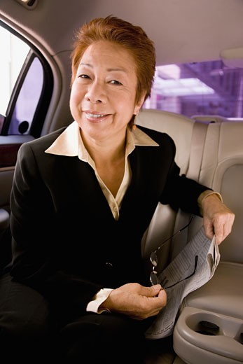 Stock Photo: 1589R-72989 Asian businesswoman in back seat of car