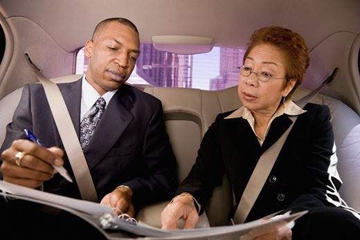 Stock Photo: 1589R-72993 Business people working in back seat of car
