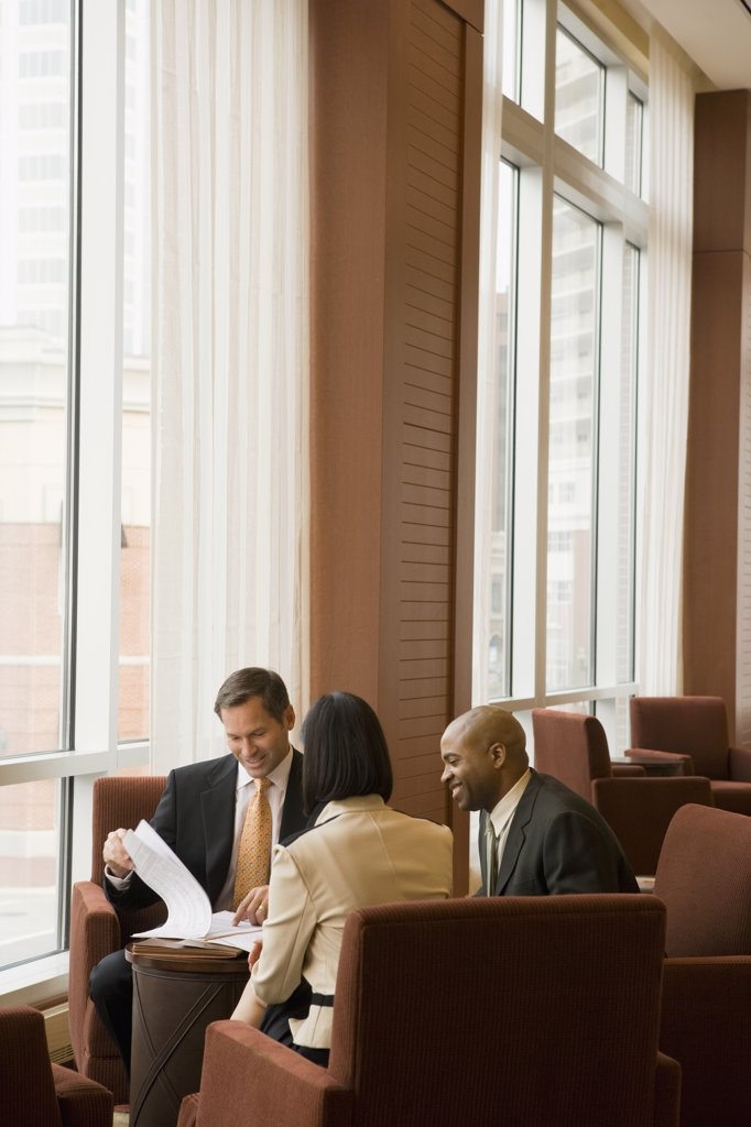 Stock Photo: 1589R-73151 Multi-ethnic business people reviewing paperwork in lobby