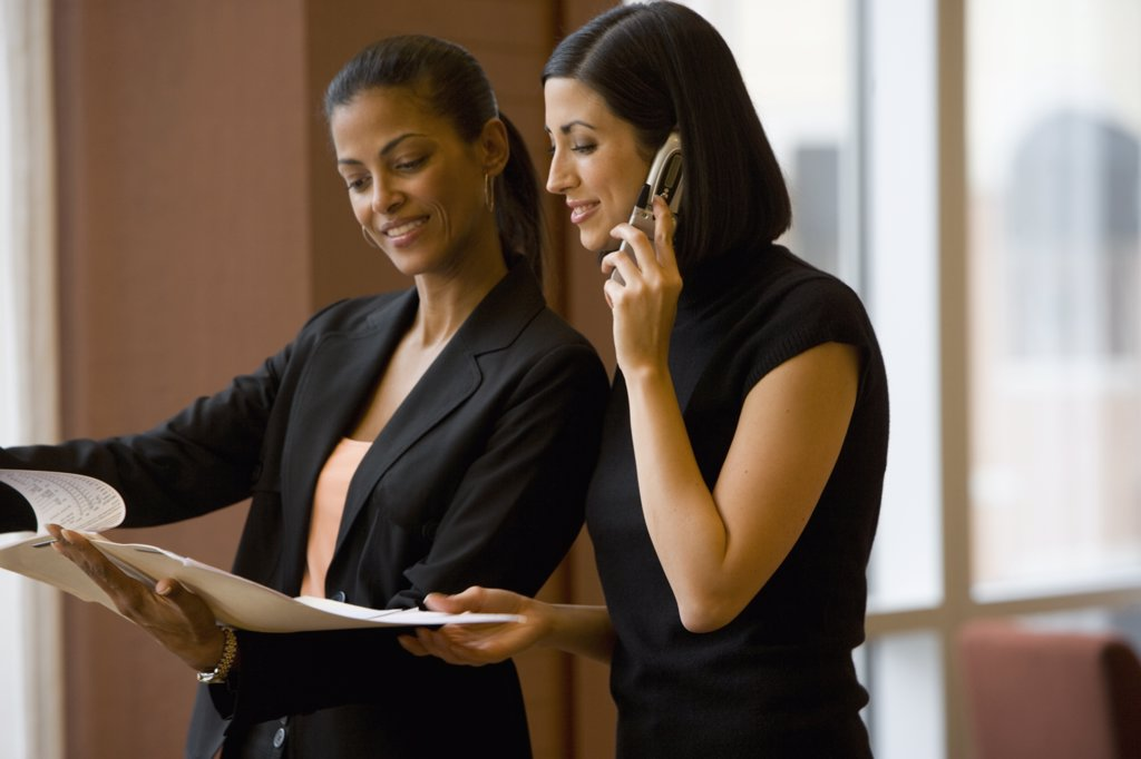 Stock Photo: 1589R-73216 Multi-ethnic businesswomen reviewing paperwork and talking on cell phone