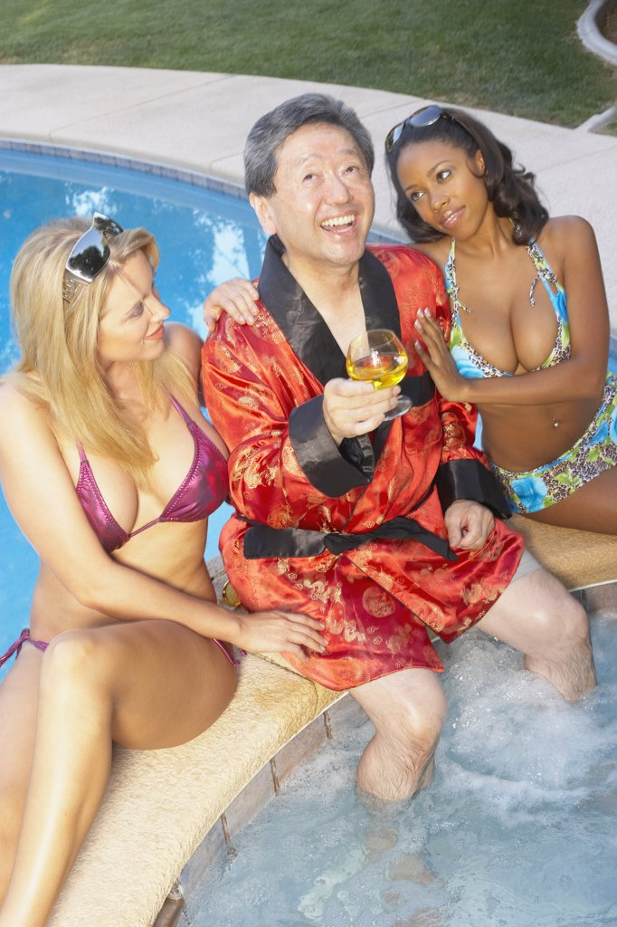 Asian playboy enjoying hot tub with young girlfriends : Stock Photo