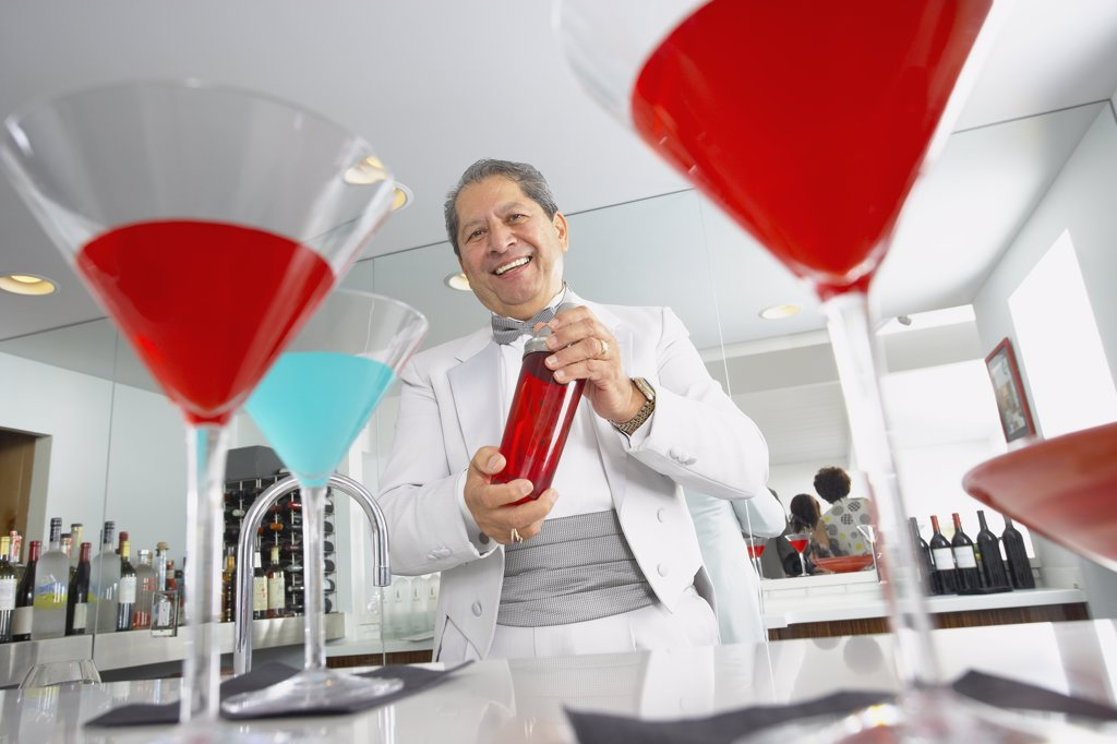 Stock Photo: 1589R-73345 Hispanic host mixing martini cocktails at party