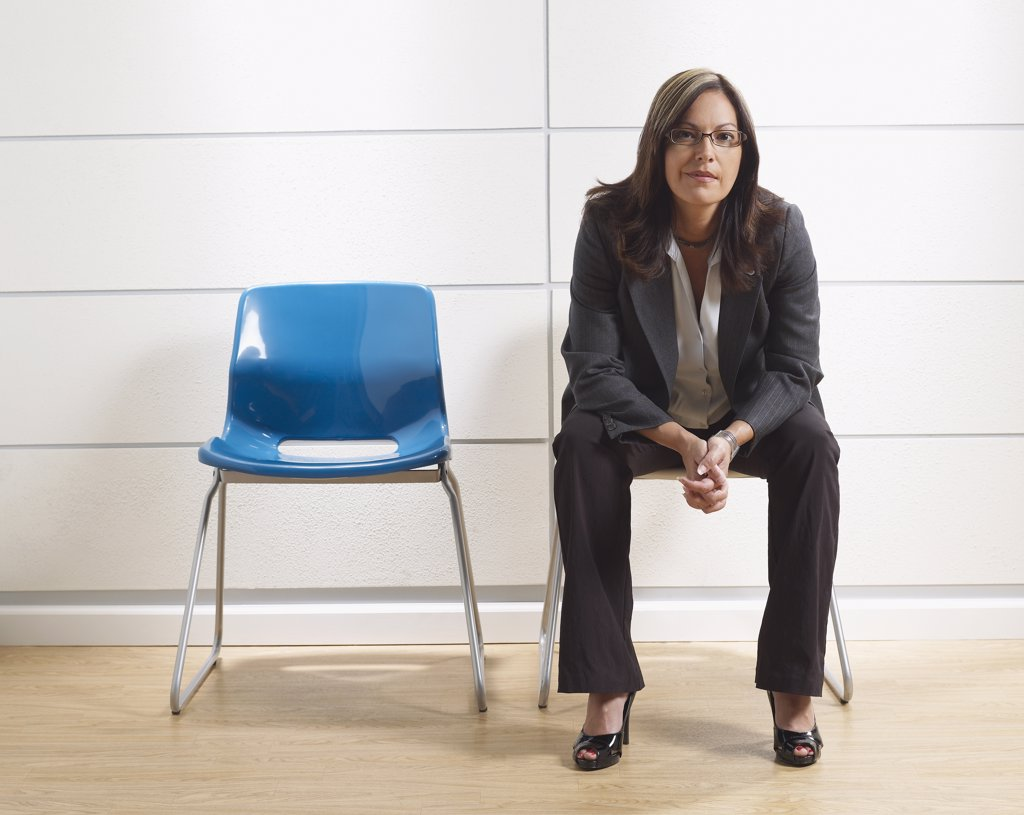 Hispanic businesswoman sitting in waiting room : Stock Photo