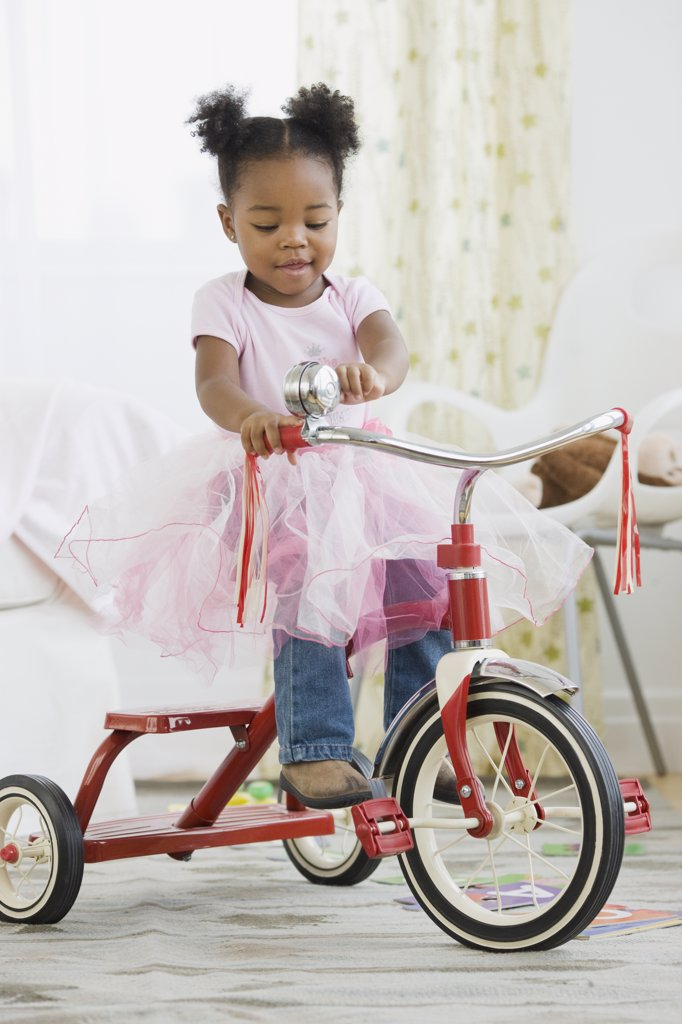 Stock Photo: 1589R-73678 African American girl in costume riding tricycle