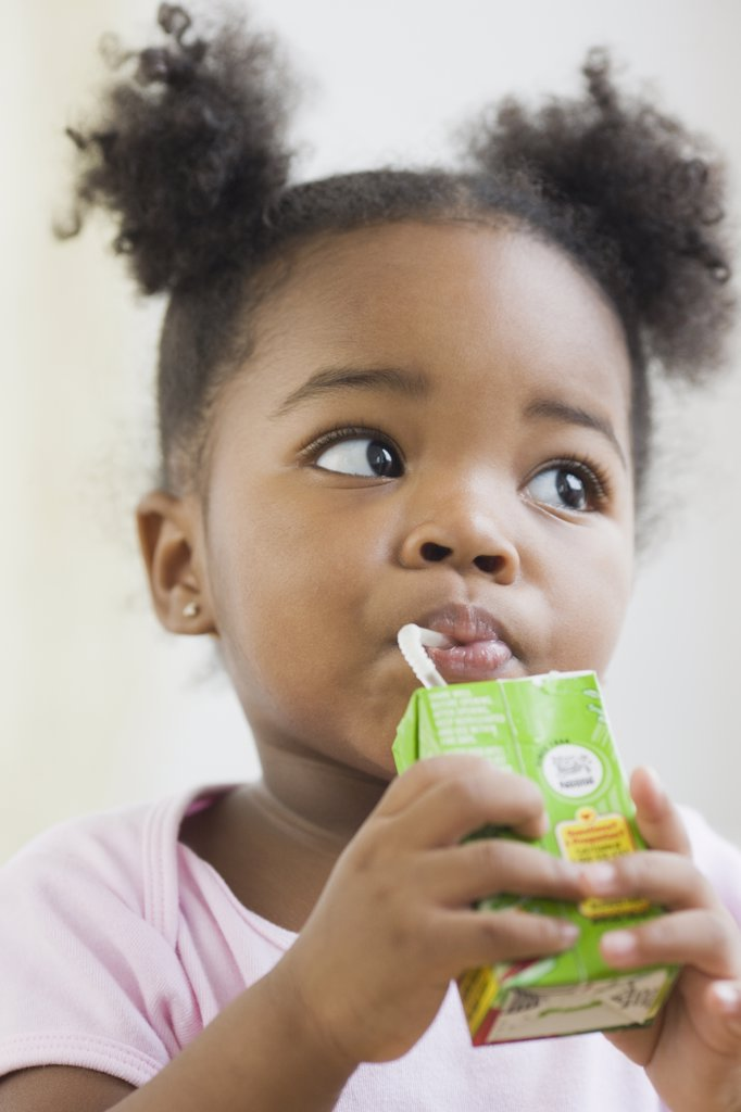Stock Photo: 1589R-73680 African American girl drinking juicebox