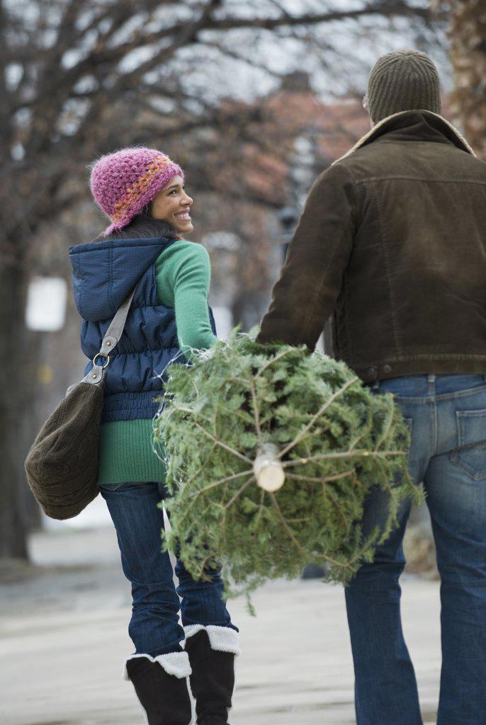 Stock Photo: 1589R-73729 Couple carrying Christmas tree